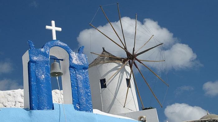 The scattered windmills in Oia